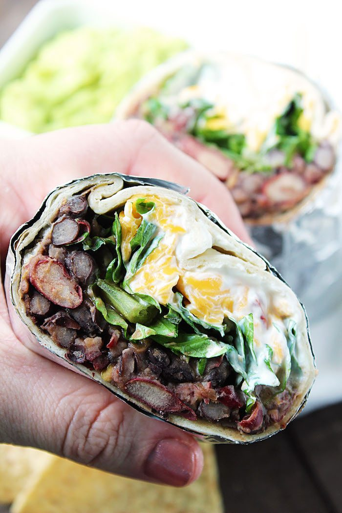 Close up shot of Chipotle Bean Burritos, in hand. High Heels and Grills