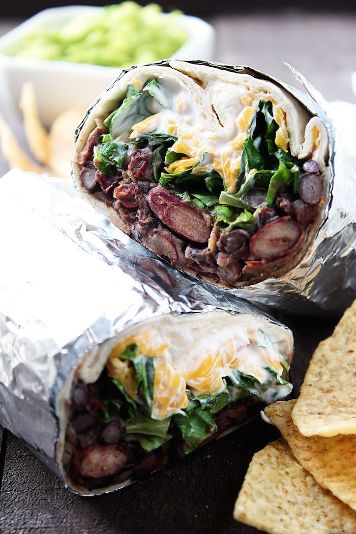 Chipotle Bean Burritos cut in half and wrapped in foil. Chips and guacamole on side. High Heels and Grills