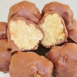 Plate of Chocolate Peanut Butter Balls with one ball cut in half, showing the insides with the rice krispy, peanut butter filling.