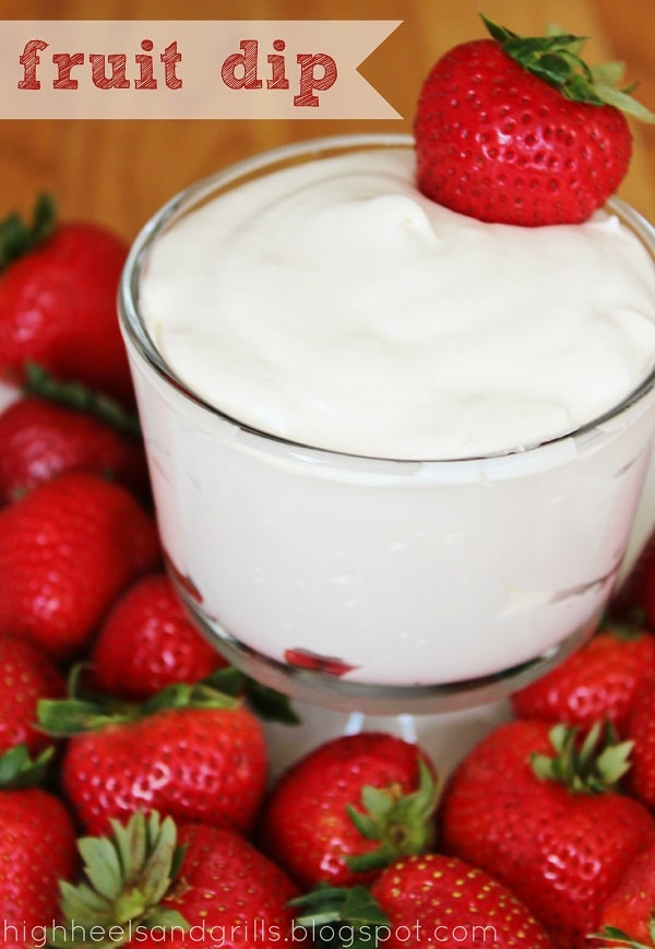 Bowl of Fruit Dip surrounded by whole strawberries.
