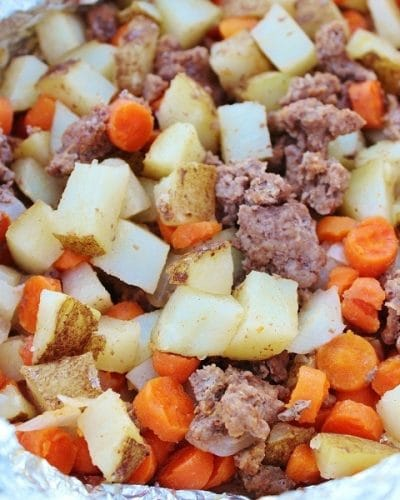Ground beef, carrots, potatoes, and onions laid out in aluminum foil to make up a tin foil dinner packet.