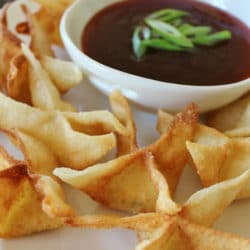 Plate of Cream Cheese Rangoons with a bowl of dipping sauce