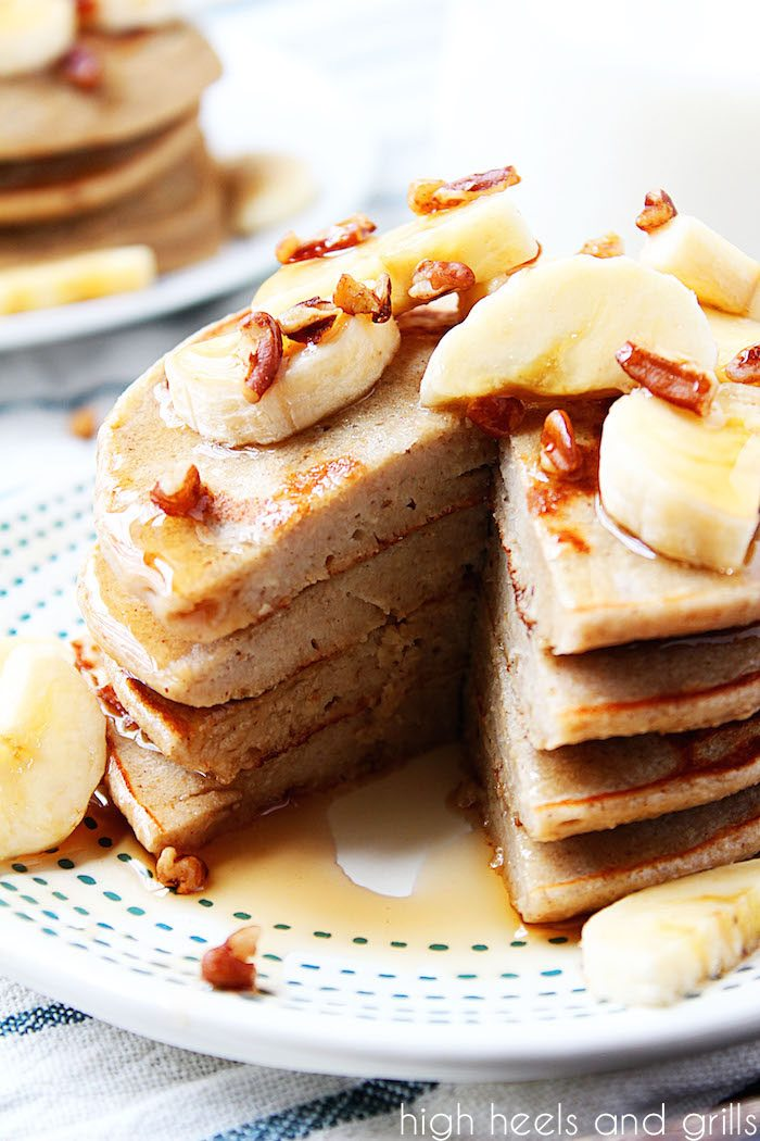 Healthy Banana Pancakes - Bite taken out of stack with bananas and pecans on top.