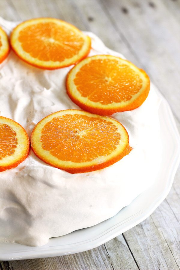 Skinny Orange Creamsicle Cake - a low calorie cake. Whole cake on plate. Whipped topping icing with orange slices on top.