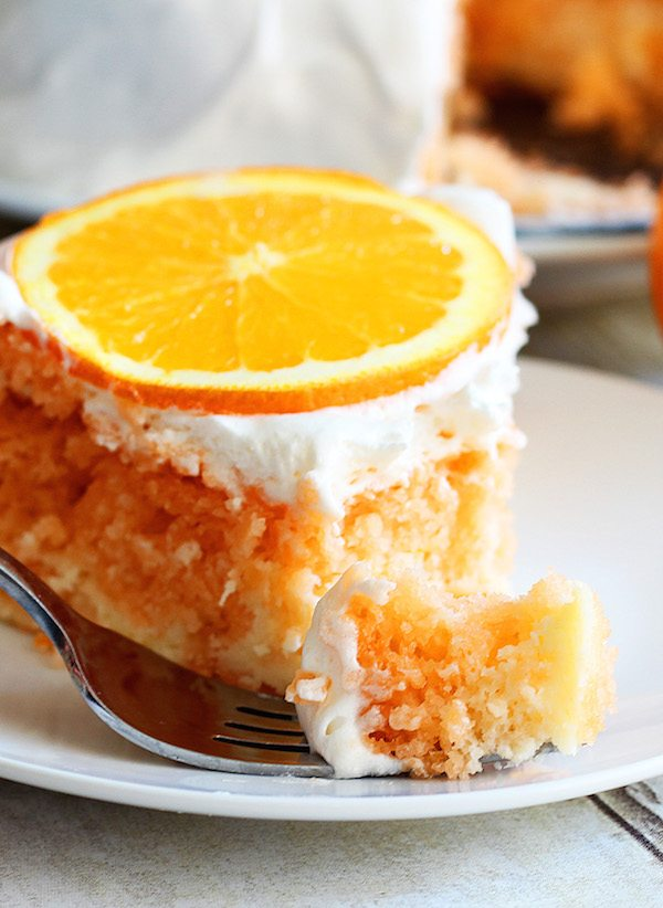 Skinny Orange Creamsicle Cake - a low calorie cake. Single slice of cake, with fork and cake piece in front.