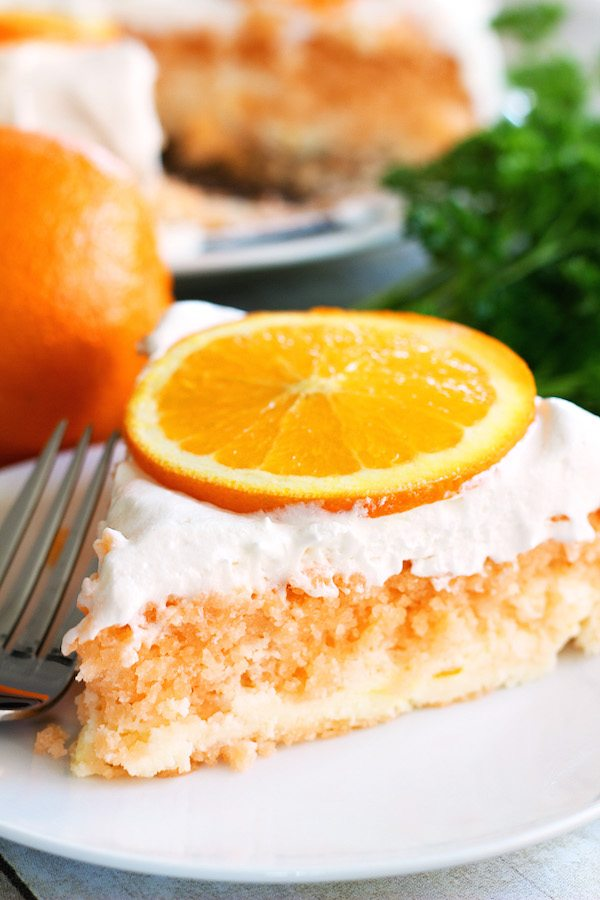 Skinny Orange Creamsicle Cake - a low calorie cake. Single slice of cake on plate, with fork, whole cake in background