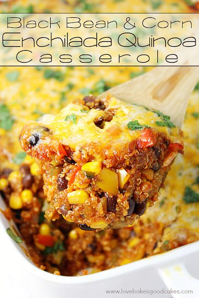 A wooden spoon holding up corn enchilada casserole to the camera.