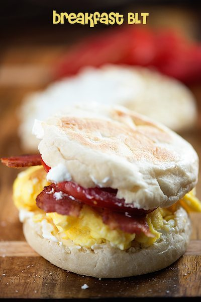 A close up of a biscuit with bacon and eggs in the middle of it.