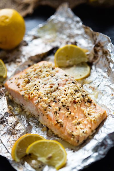 Salmon fillet on a large piece of tin foil surrounded by lemon wedges.