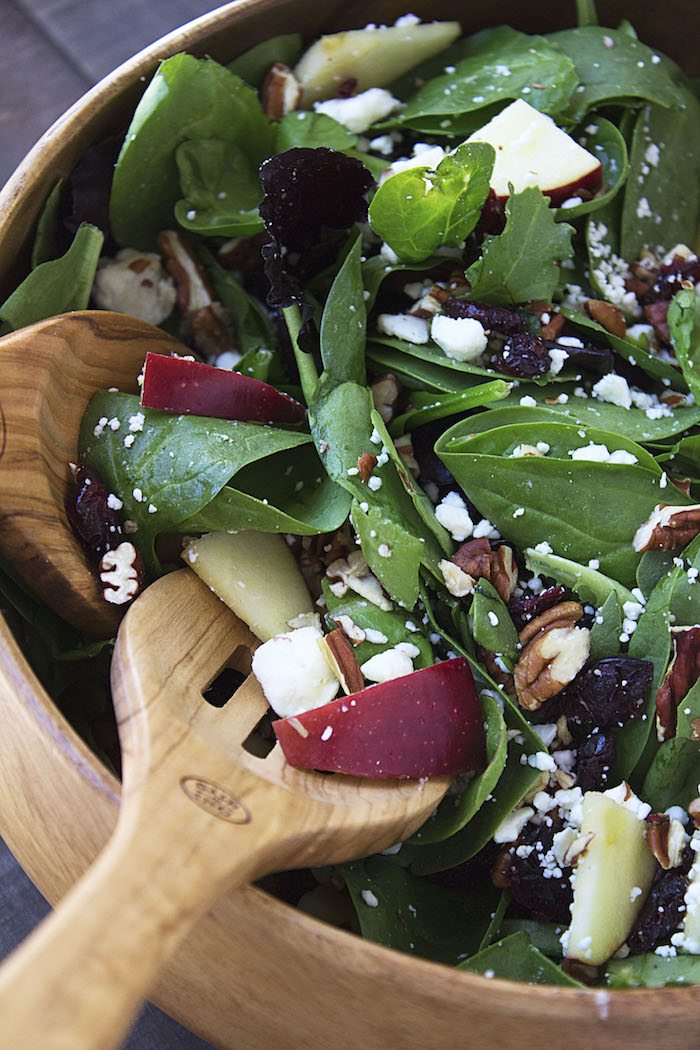 Apple Cranberry Feta Pecan Salad in a bowl with salad spoons. Thanksgiving side dish.