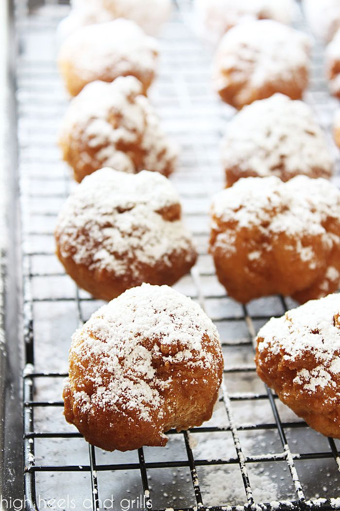 Big batch of biscuit beignets resting on a cooling rack after being freshly topped with powdered sugar.