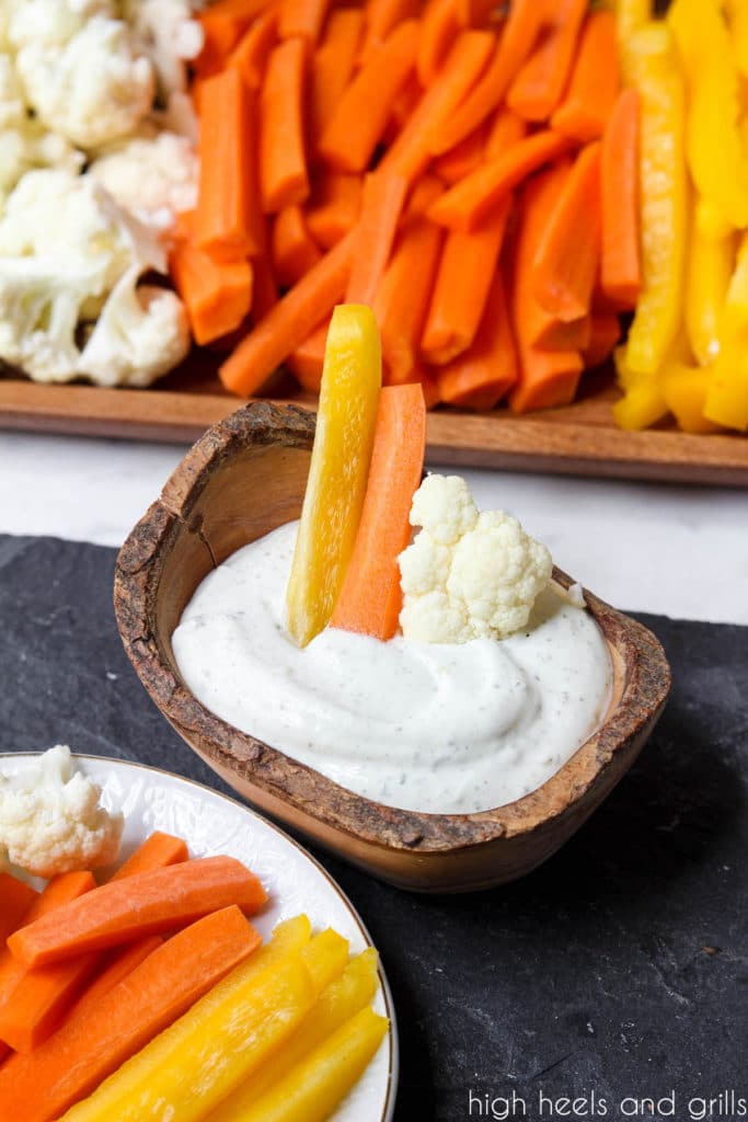 Yellow pepper, orange carrot, and white cauliflower sticking out of a bowl of dip to look like a Candy Corn Halloween Veggie Tray