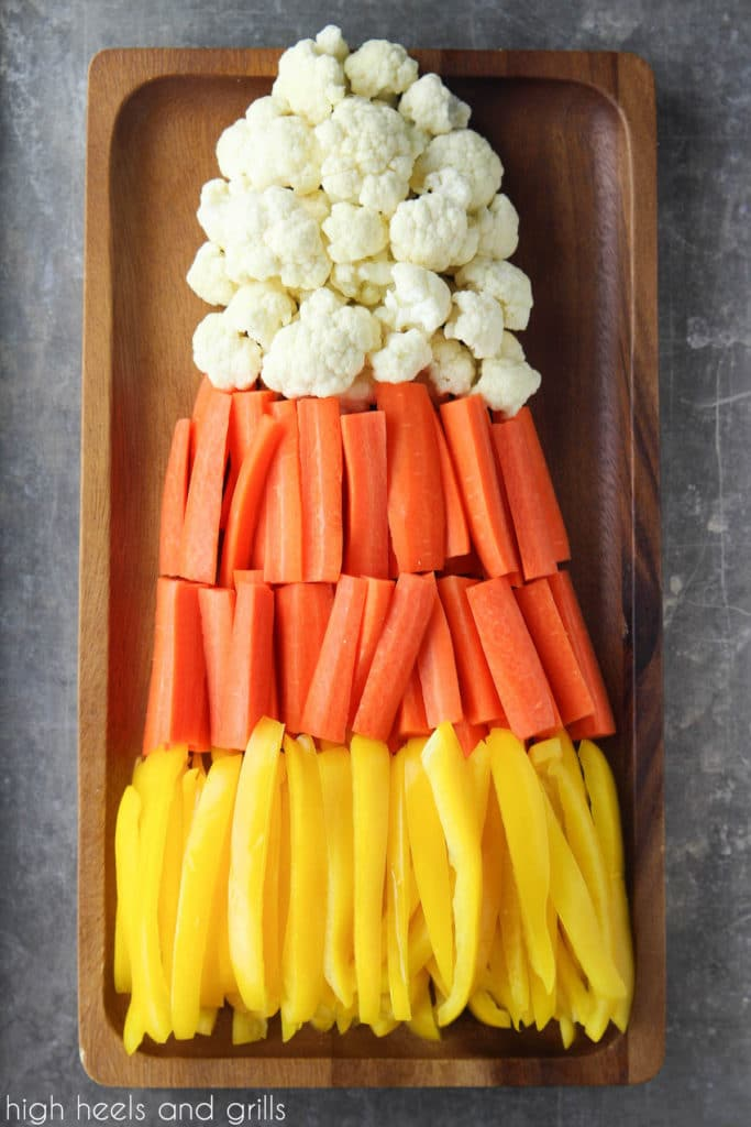 Candy Corn Halloween Veggie Tray with yellow peppers on the bottom, orange carrots in the middle, and white cauliflower on top. Shaped in a triangle to look like candy corn