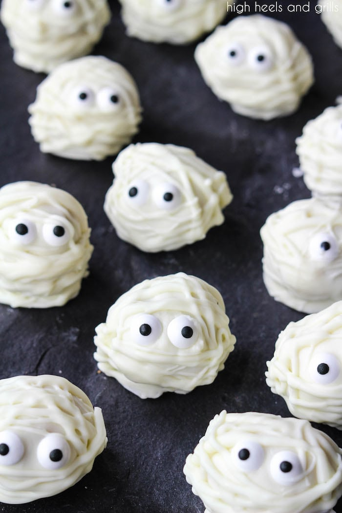 Easy Halloween Treat Donut Hole Mummies spread out on a platter.