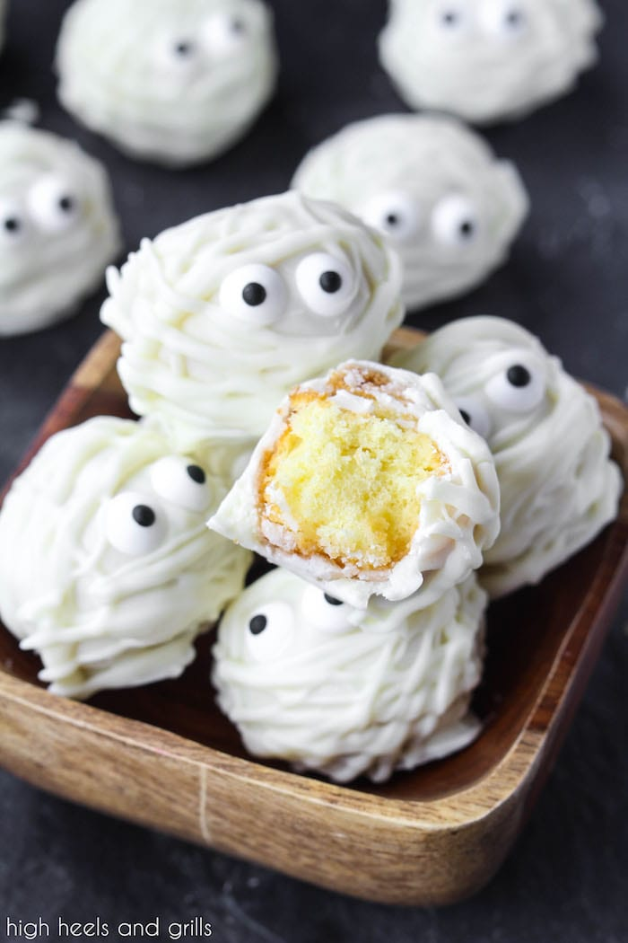 Small bowl of Easy Halloween Treat Donut Hole Mummies with one cut in half, showing the donut hole inside.