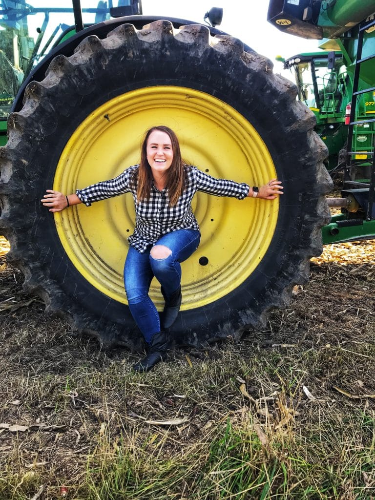 Sarah Averett in a tractor wheel on a corn farm in Iowa.