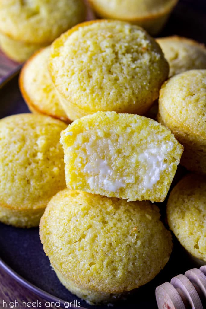 A pile of sweet cornbread muffins with honey drizzled on the tops. The middle one split in half with butter soaking into it.