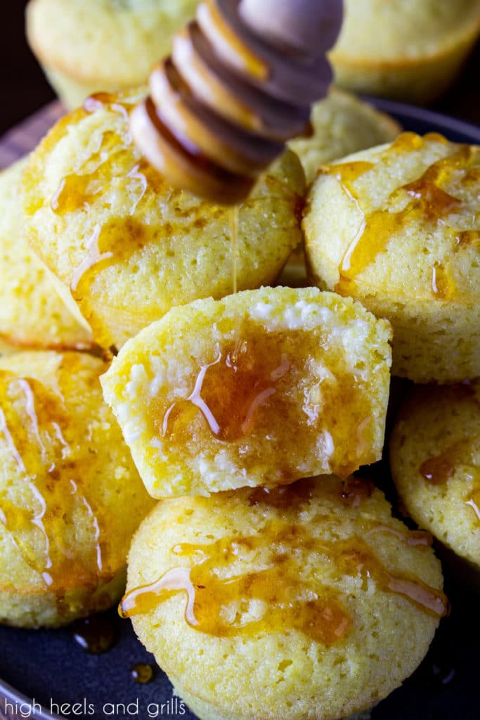 A pile of sweet cornbread muffins with honey drizzled on the tops. The middle one split in half, butter slathered on it, and honey being drizzled from a honey dipper.